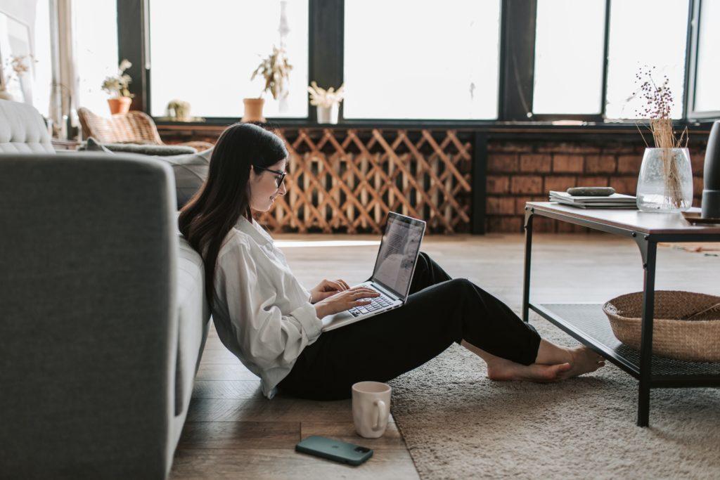 ライターは自宅で気ままにできる魅力がある(くつろげる空間で記事を書く女性)